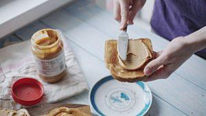 Девушка готовит бутерброд с арахисовой пастой