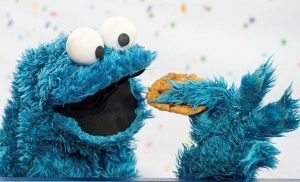Куки монстр ест вкусное имбирное печенья.