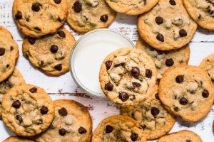 Много печенья с шоколадной крошкой у стакана молока.