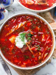 Красный кето борщ в тарелке со сметаной.