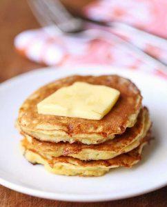 Кето сырники с арахисовой пастой нервированы на тарелке со сливочным маслом.