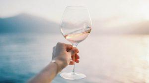 Кето вино в бокале на фоне моря.